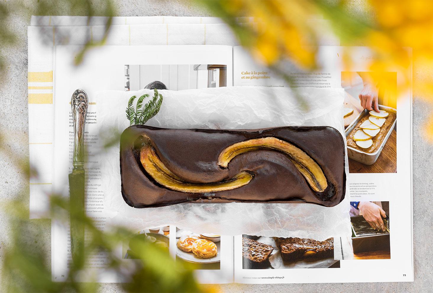 Une recette facile de banana bread protéiné au chocolat en flatlay, réalisé avec le Fit Chocolate de Natural Mojo, posé sur un magazine culinaire ouvert sous des fleurs jaunes