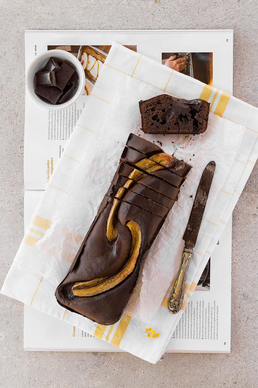 Un banana bread protéiné au chocolat, posé sur un magazine avec un couteau et des carreaux de chocolat, dont les parts sont coupées