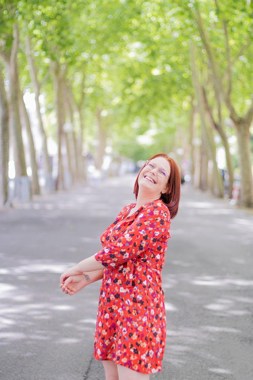 Une robe rouge fleurie pour l'été, portée avec le sourire sur le boulevard verdoyant de Tours