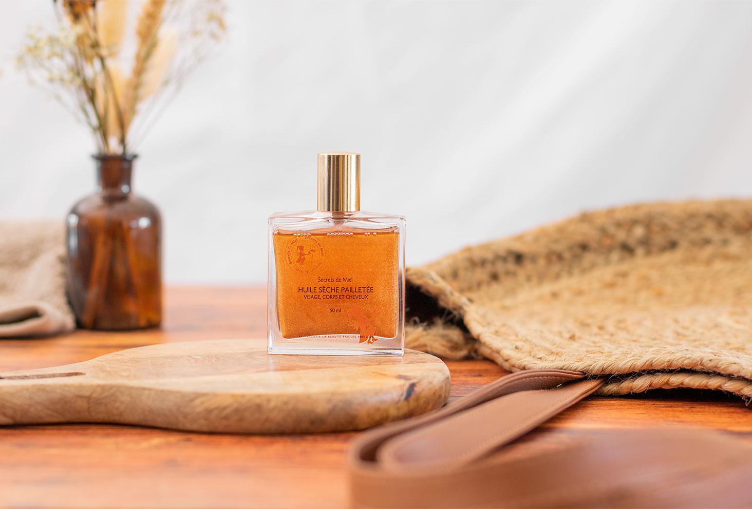 L'huile sèche à paillettes de Secrets de Miel posée sur une planche à découper devant un sac de plage