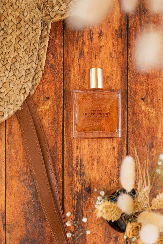 L'huile sèche pailletée de Secrets de Miel posée sur une table en bois avec des fleurs séchées et un sac de plage