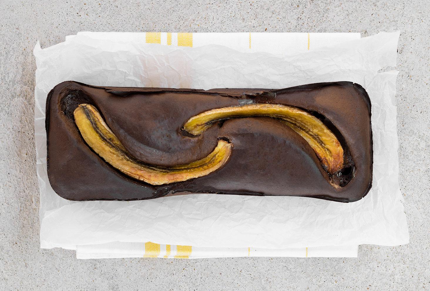 Zoom sur le banana bread protéiné avec le Fit Chocolate de Natural Mojo, posé sur un torchon et un fond en béton