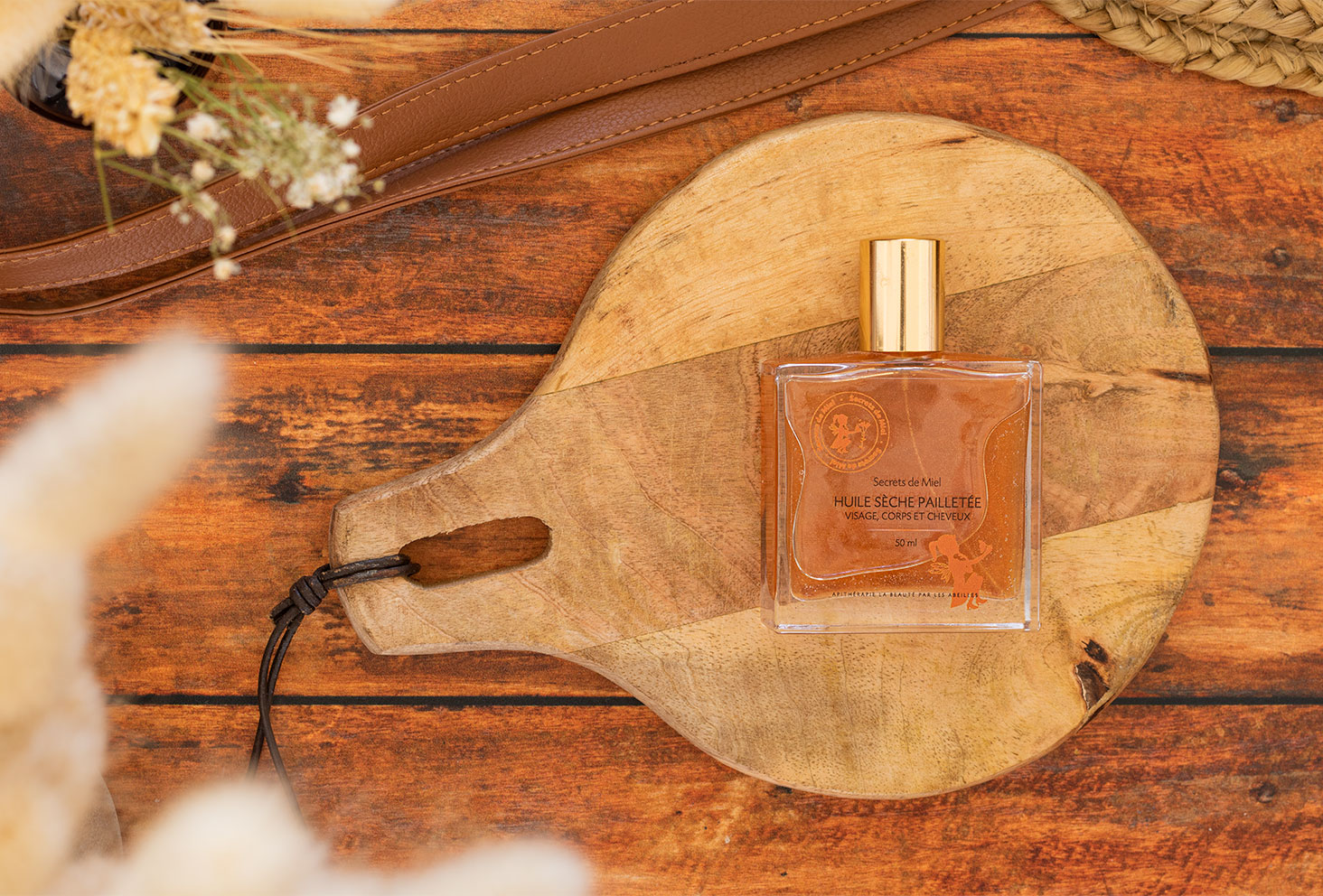 Zoom sur l'huile sèche pailletée de Secrets de Miel posée sur une planche à découper en bois