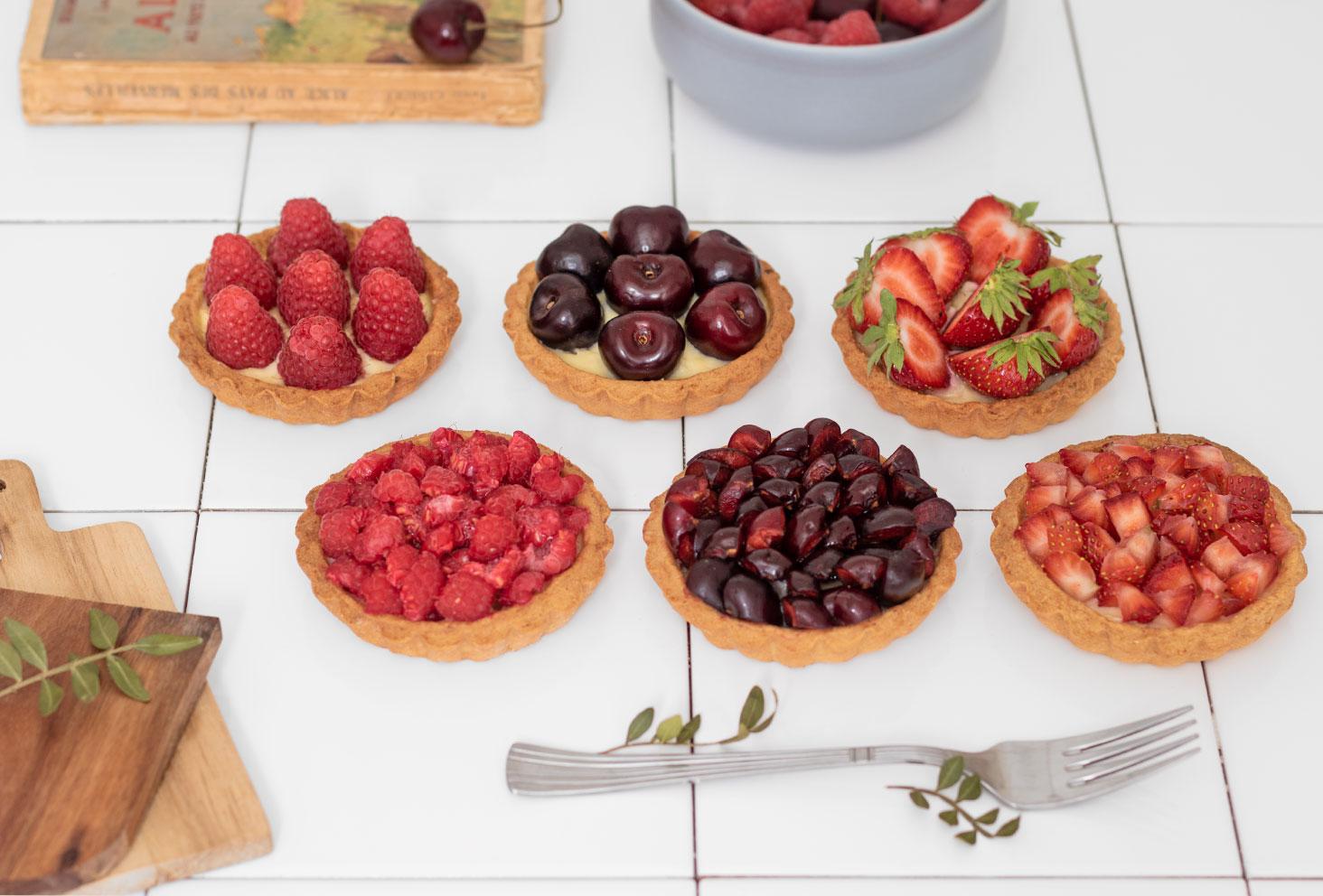Des tartelettes aux fruits rouges posées sur un carrelage dans une cuisine