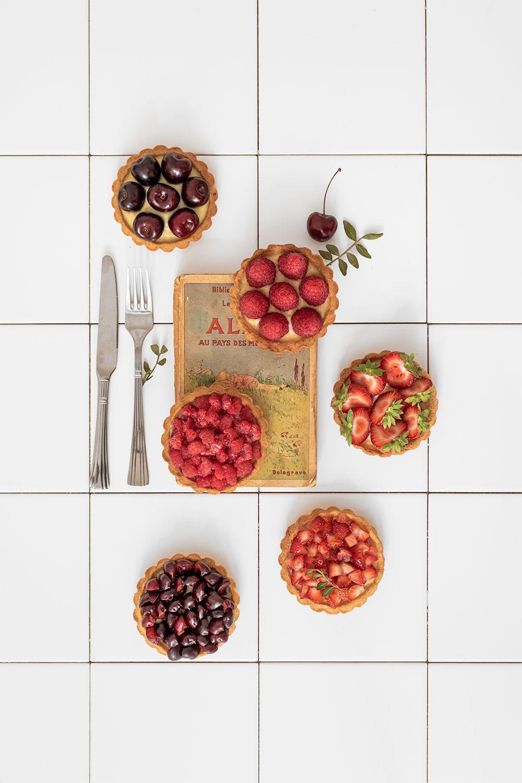 Stylisme culinaire de tartelettes aux fruits rouges sur un fond en carrelage blanc