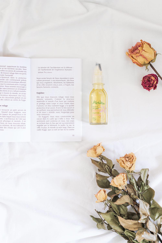L'huile d'argan à l'huile essentielle de rose de Melvita posée sur un drap blanc à côté d'un livre au milieu de roses séchées
