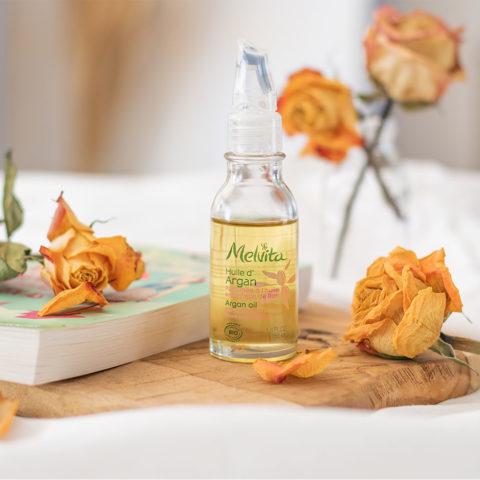 L'huile d'argan à la rose de Melvita sur une planche à découper en bois posée à côté d'un livre et de roses séchées