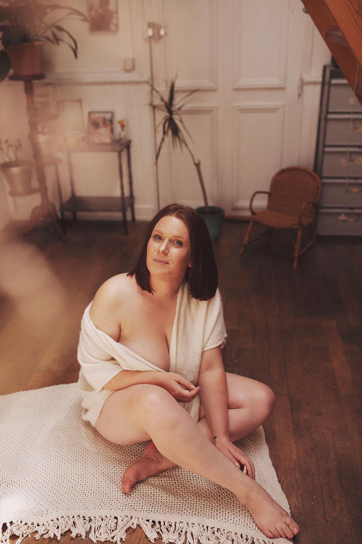 Assise sur un plaid sur le sol, dans un gilet en laine, au milieu d'un salon au parquet en bois