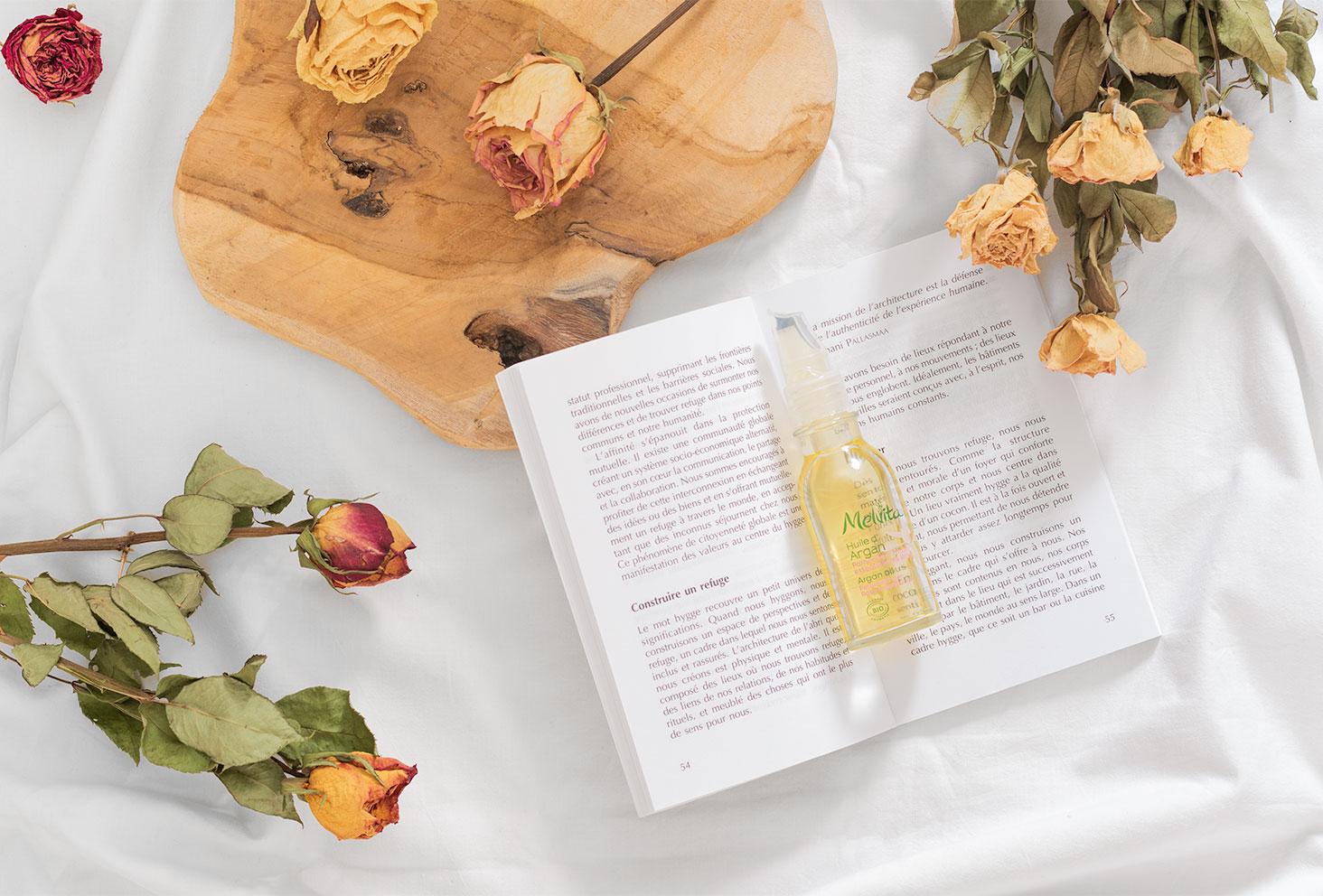 L'huile d'argan à l'huile essentielle de rose de Melvita posée sur un livre ouvert sur un lit au milieu de roses séchées