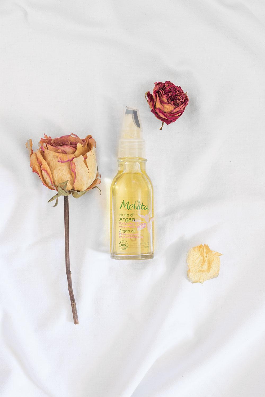 L'huile d'argan à l'huile essentielle de rose de Melvita posée sur un drap blanc au milieu de roses séchées