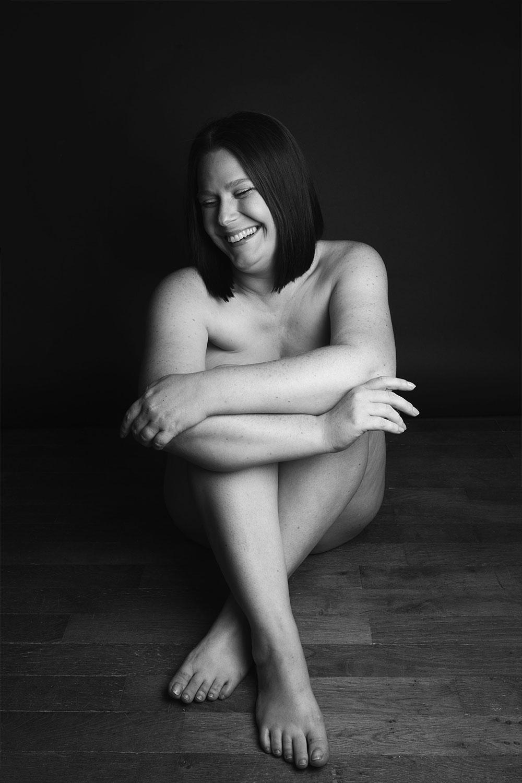 Photo de nu en studio noir et blanc avec le sourire assise sur un parquet en bois