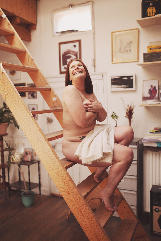 Nue dans une pièce lumineuse, assise sur un escalier en bois avec le sourire