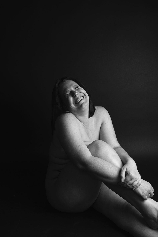 En noir et blanc assise au sol nue avec le sourire