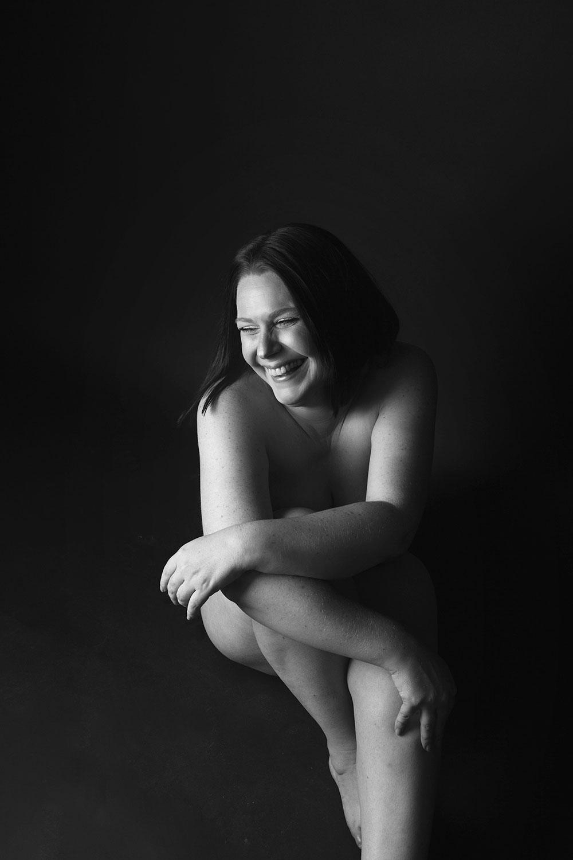 Photo de nu en noir et blanc dans un studio avec le sourire