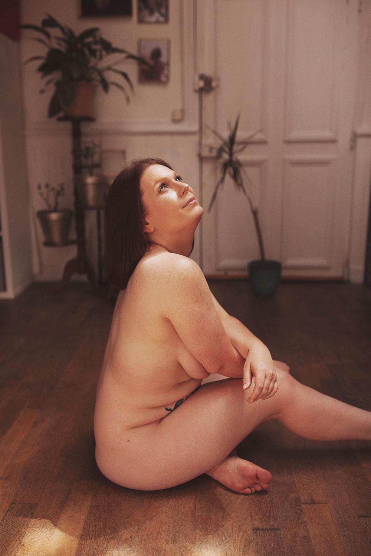 Assise nue sur un parquet en bois au milieu d'un salon vintage