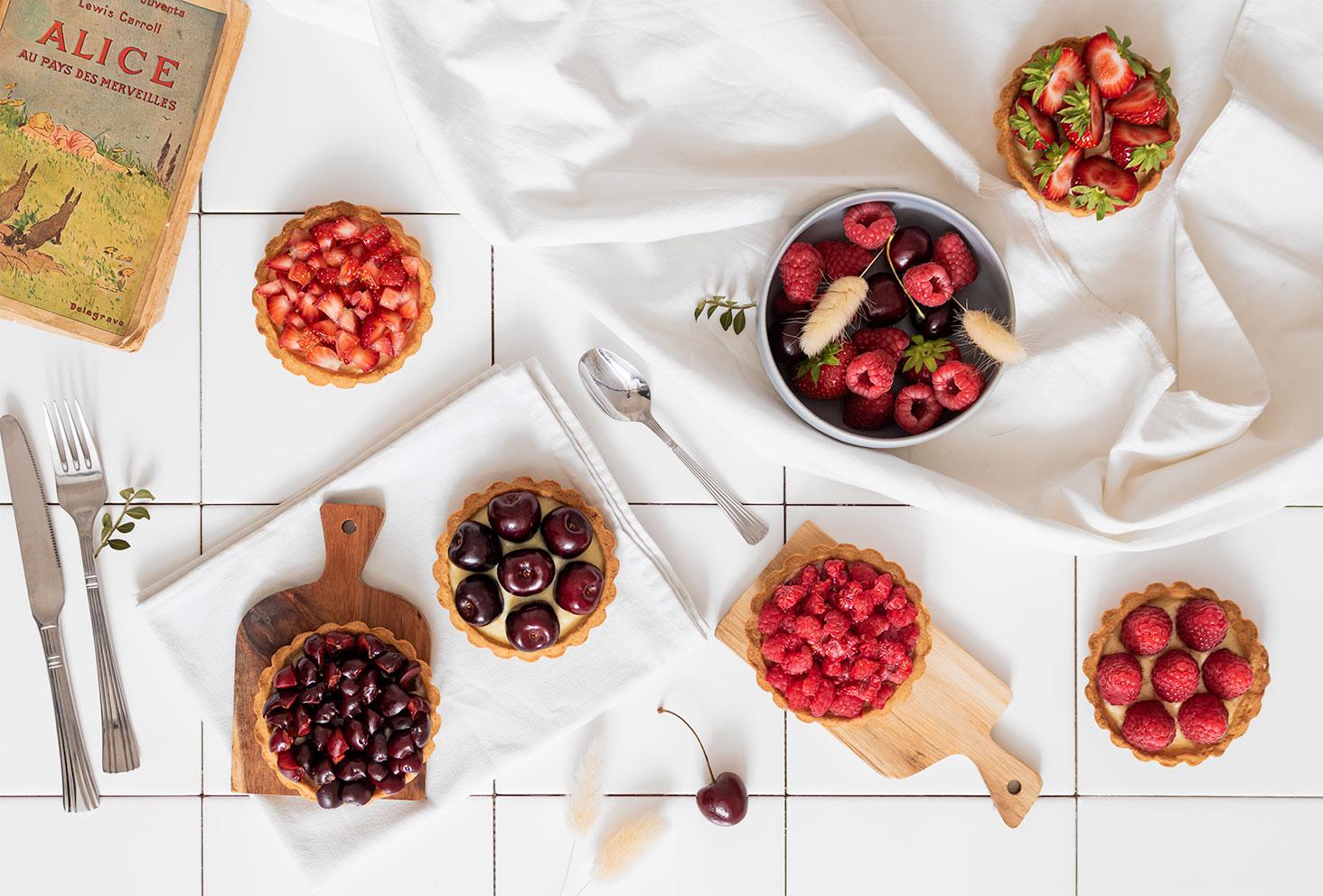 Des tartelettes aux fruits rouges sur un fond en carrelage blanc avec des couverts et des planches à découper en bois