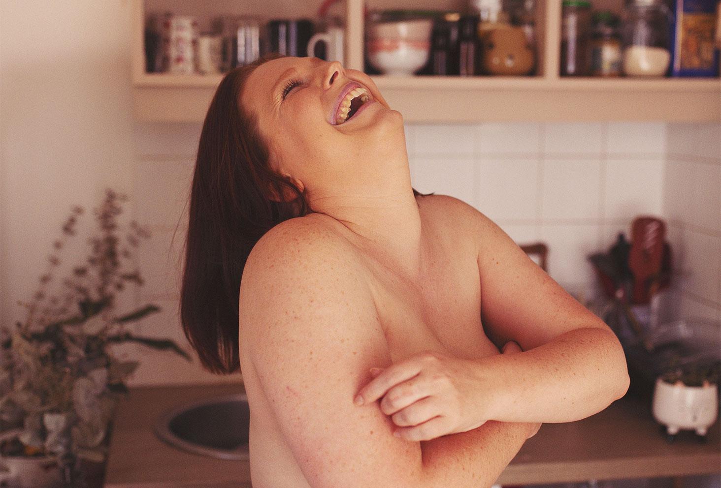 Nue dans une cuisine avec le sourire