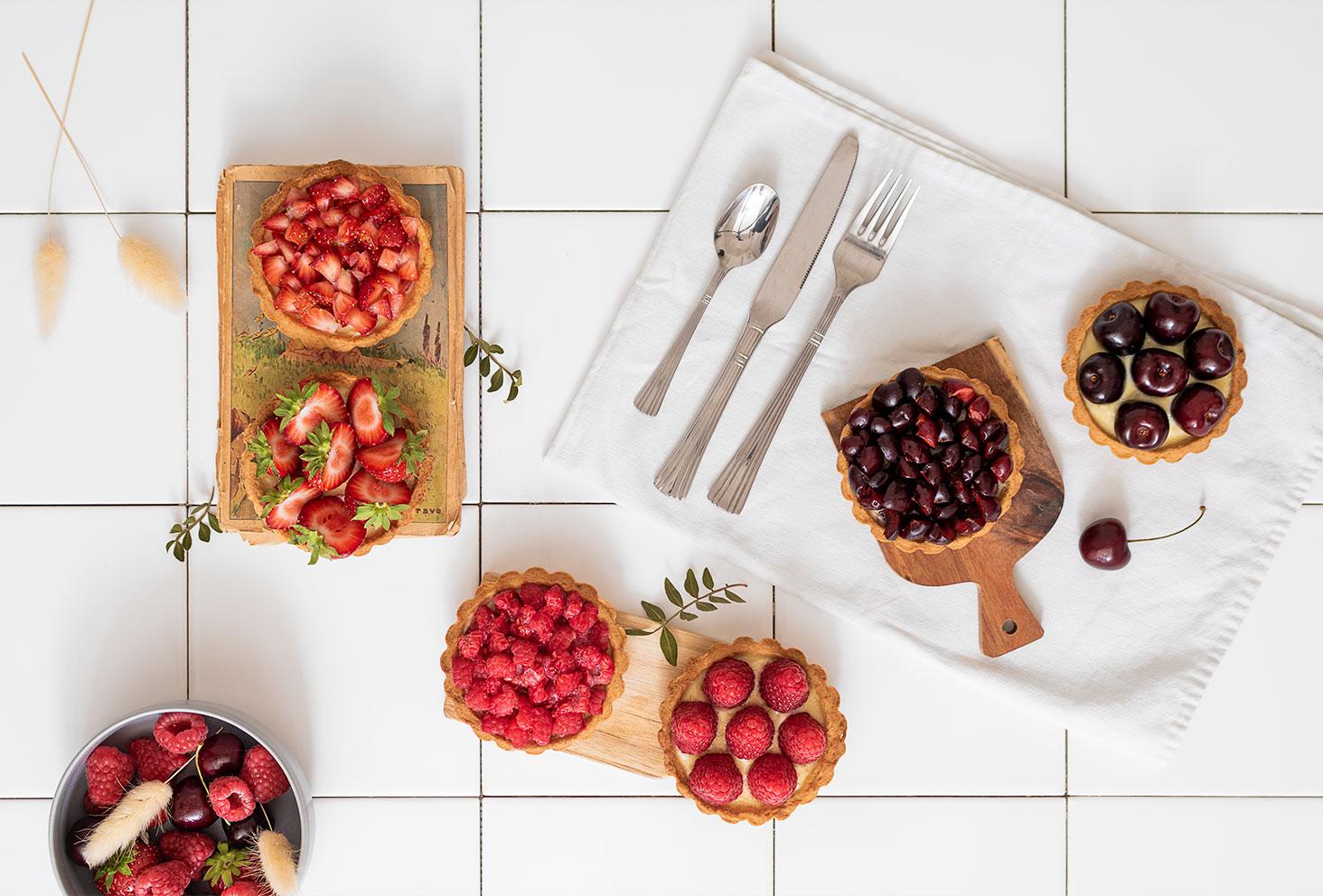 Ensemble de tartelettes aux fruits rouges sur un torchon blanc sur du carrelage de cuisine