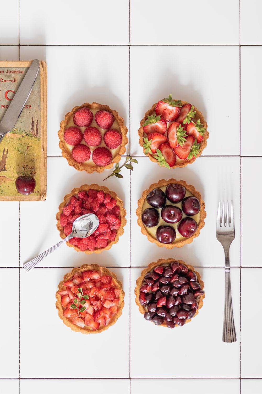 Flatlay de tartelettes aux fruits rouges sur du carrelage de cuisine blanc