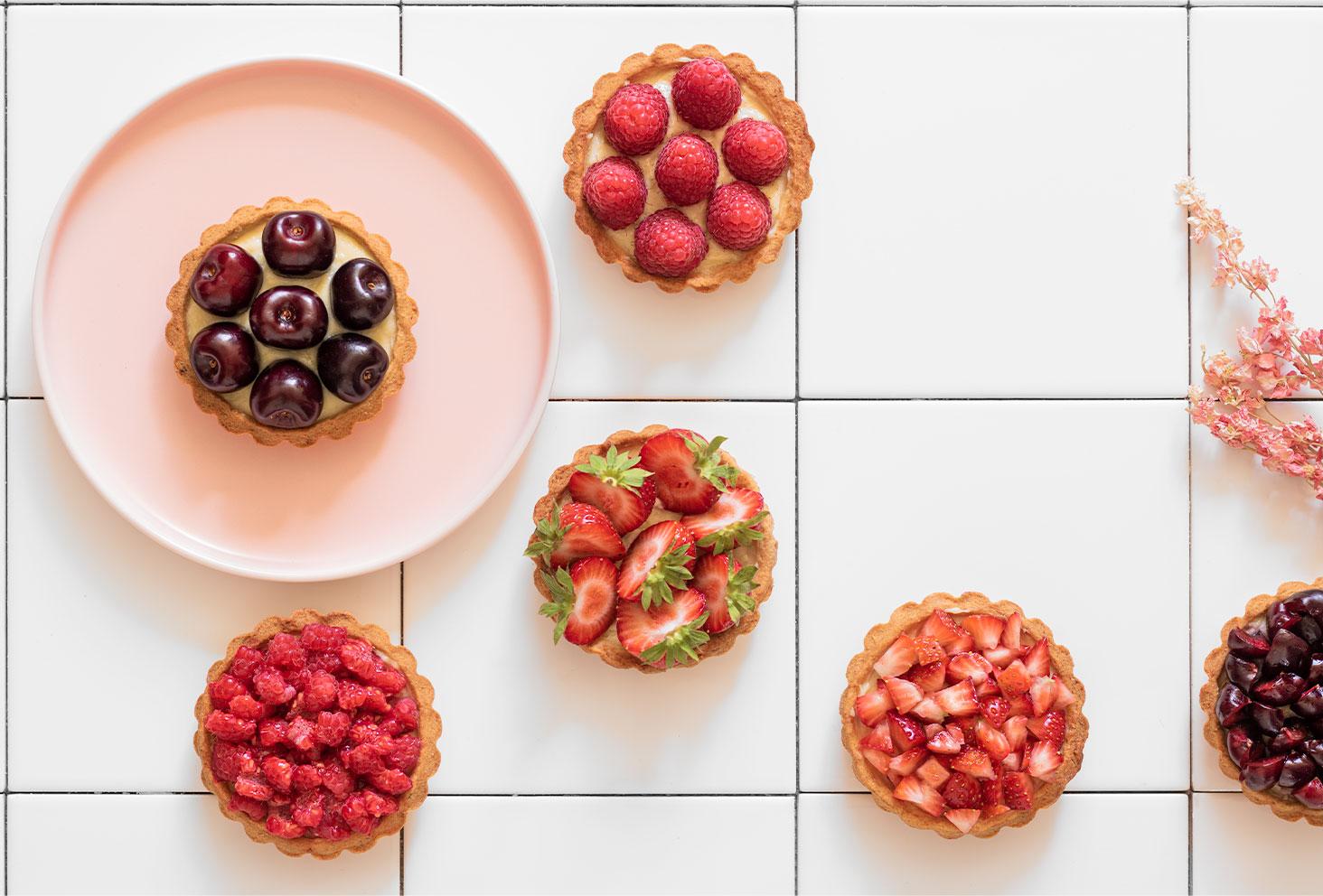 Plusieurs tartelettes aux fruits rouges posées dans une assiette rose sur du carrelage blanc