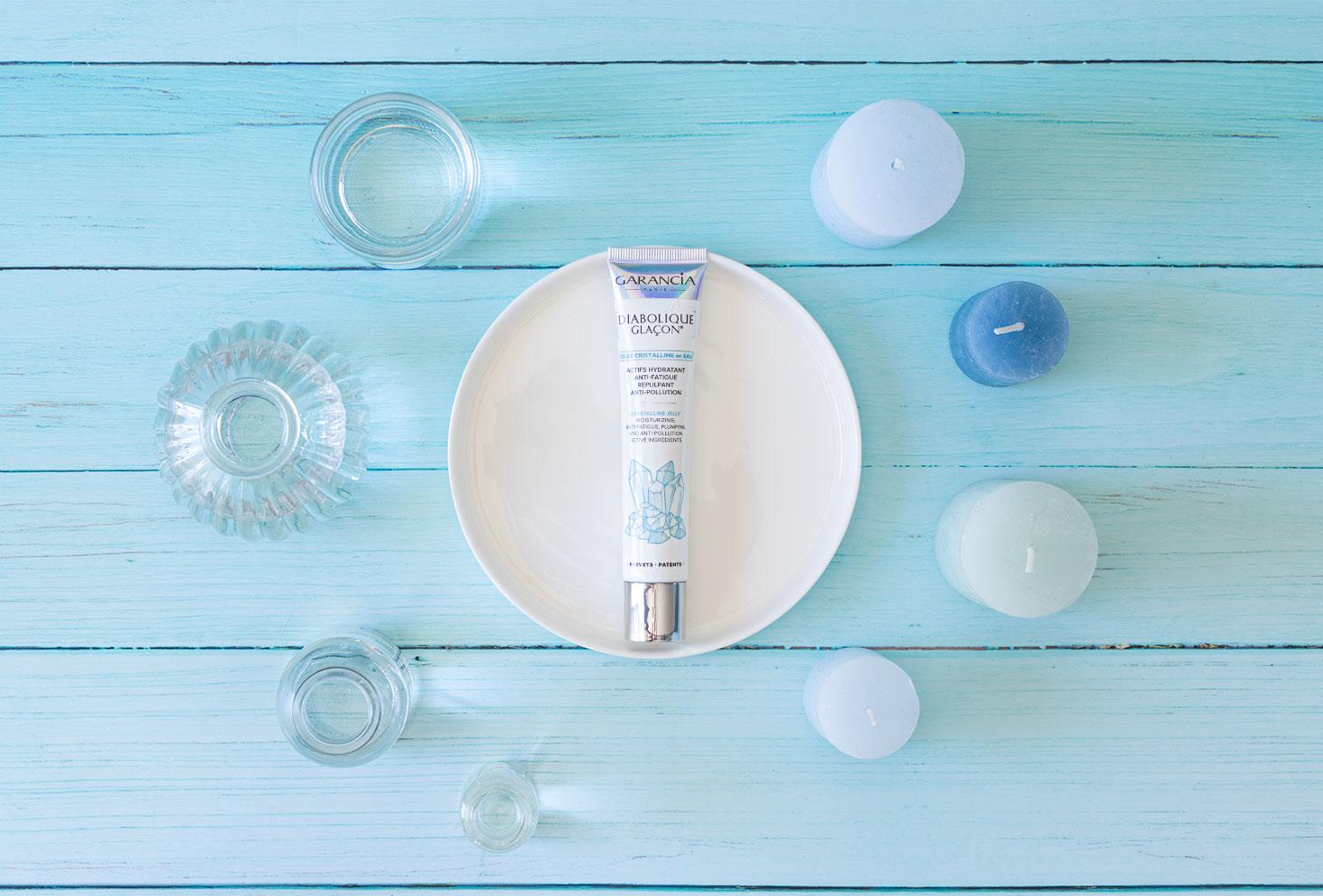 Le Diabolique Glaçon de Garancia posé dans une coupelle en verre blanche au milieu de bouteille en verre pleines d'eau et de bougies bleues sur un fond en bois turquoise