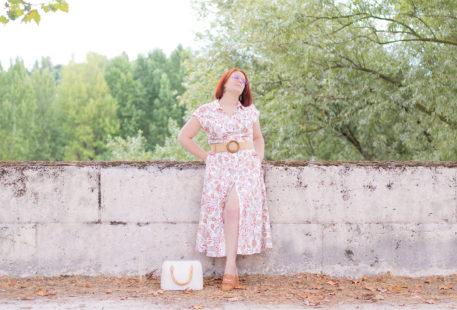 Appuyée le long d'un mur en pierre sur les bords de Loire, en robe longue en lin, les mains dans les poches à regarder au loin