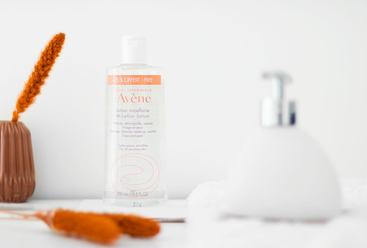 La lotion micellaire Avène posée dans une salle de bain blanche au milieu de fleurs séchées oranges