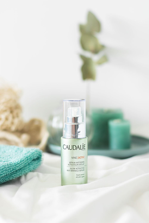 Le sérum antirides de Caudalie dans un décor vert et blanc de salle de bain