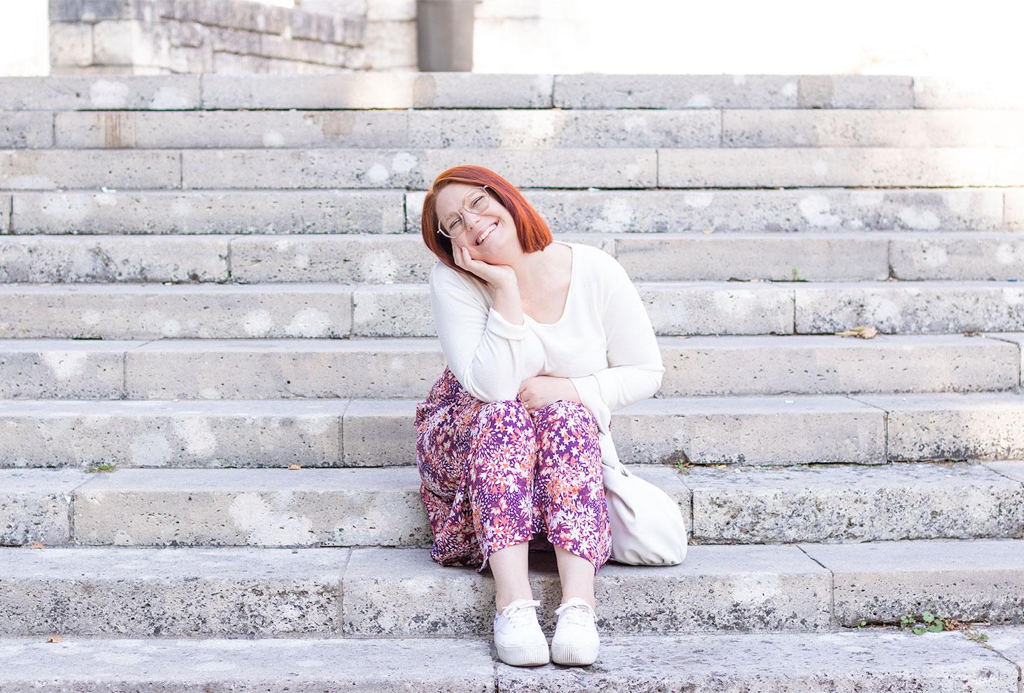 Assise dans des marches en pierre, la tête penchée posée dans la main, avec le sourire