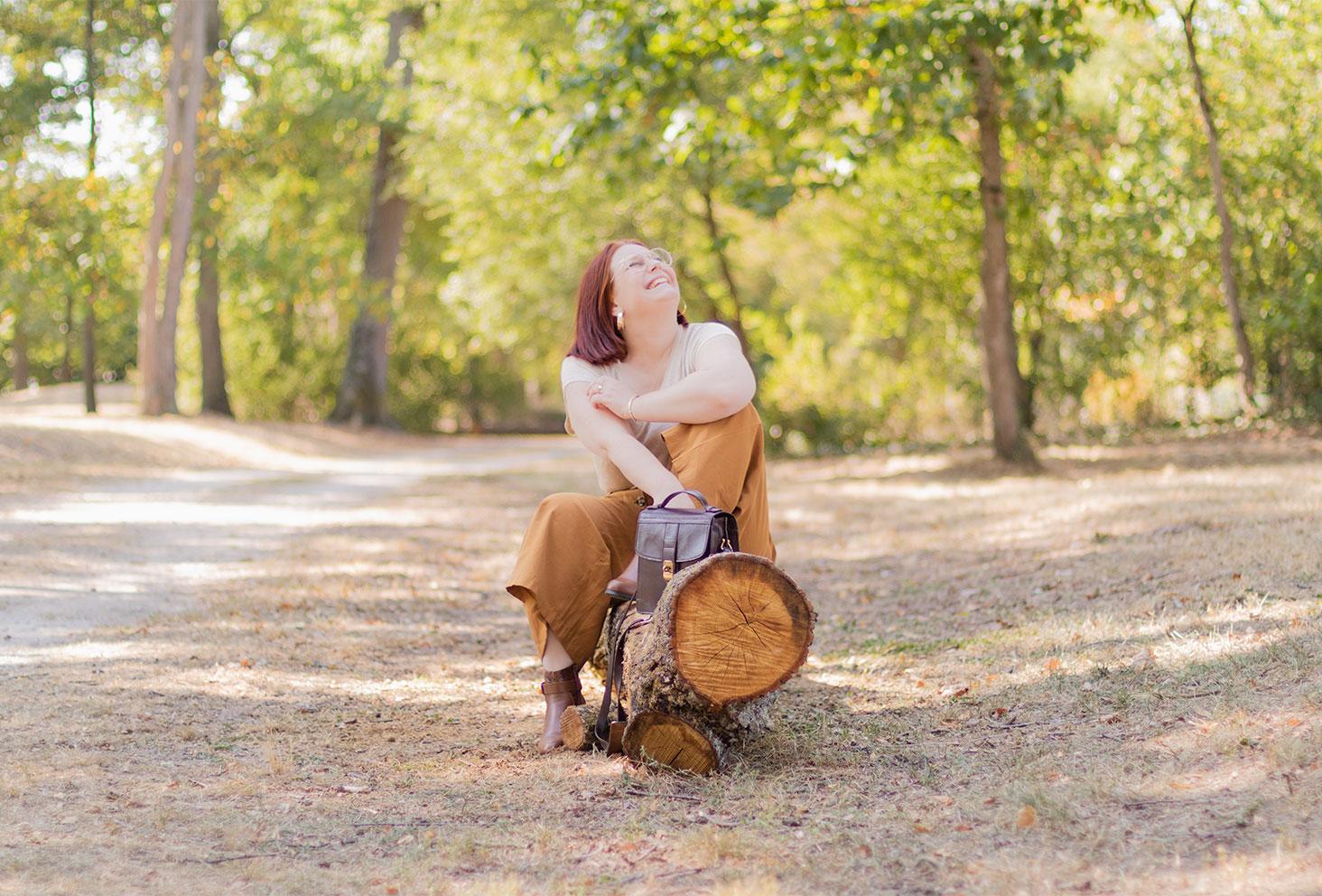 Assise sur un tronc d'arbre banc avec le sourire, la tête vers le haut, un sac vintage en cuir marron posé sur le banc également