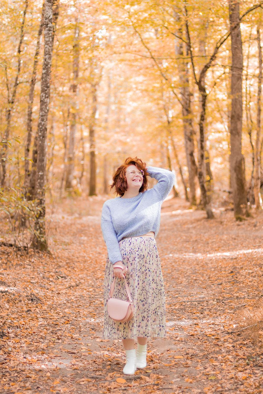 Au milieu des bois en jupe et pull pastel, avec le sourire et une main dans les cheveux