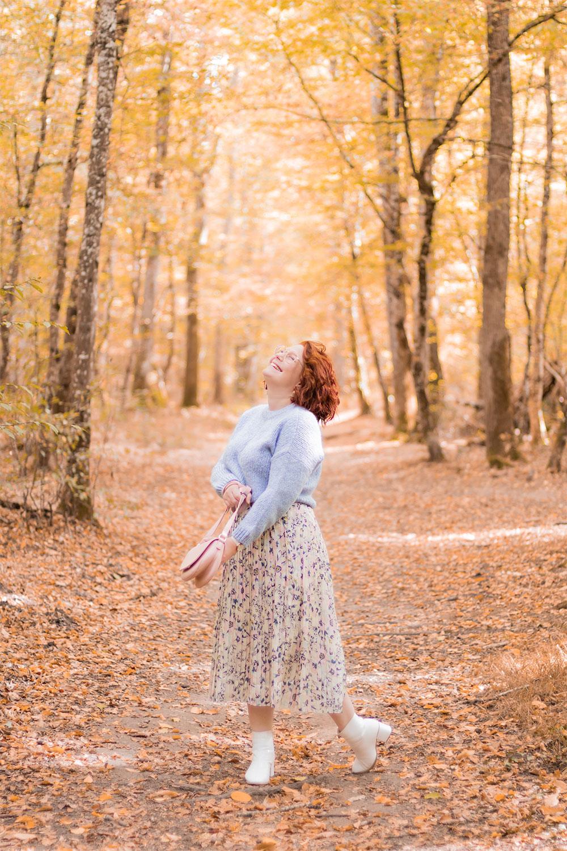 Au milieu des bois aux couleurs d'automne, avec le sourire, en total look pastel