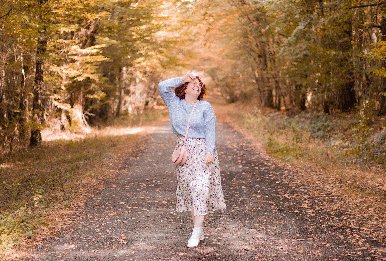 Dans une allée au milieu des bois, une main sur la tête avec le sourire, en jupe longue et pull en laine bleu pastel