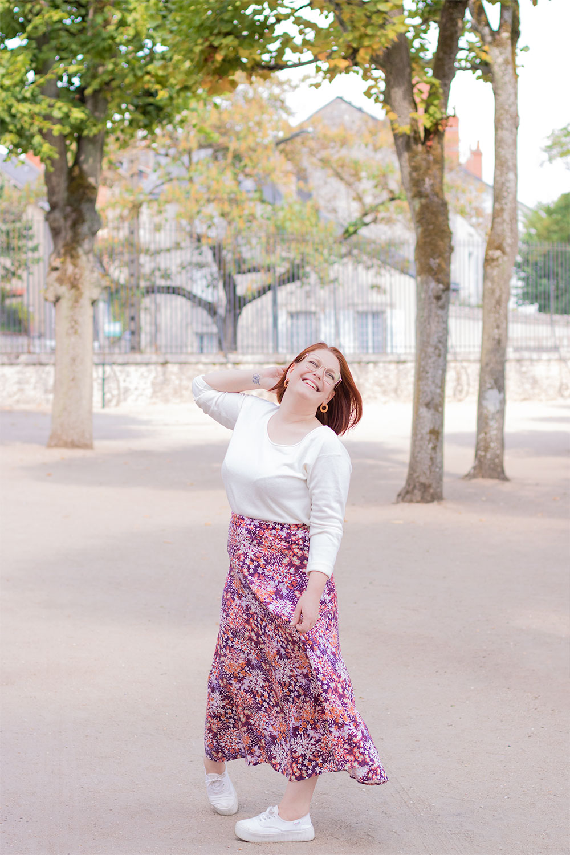 Dans un parc en jupe longue et pull blanc, avec le sourire et une main dans les cheveux