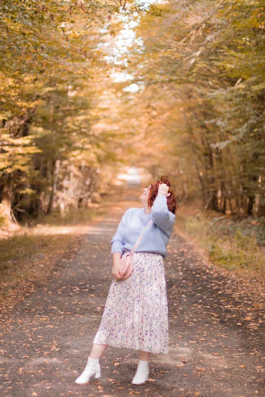 Au milieu d'une forêt d'automne en couleurs pastel, jupe longue fluide et pull bleu en laine, de profil une main dans les cheveux