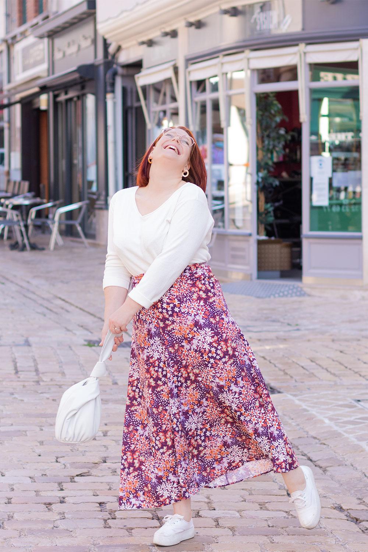 Dans la rue la tête vers le haut avec le sourire, en jupe longue à fleurs et pull blanc, le sac vers l'avant entre les mains