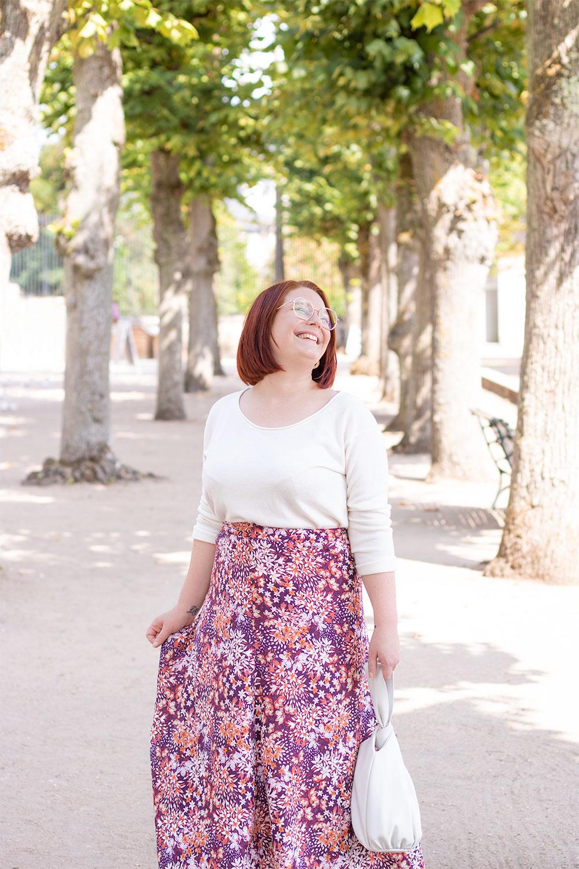 En pull blanc léger et jupe longue rose dans un parc, avec le sourire