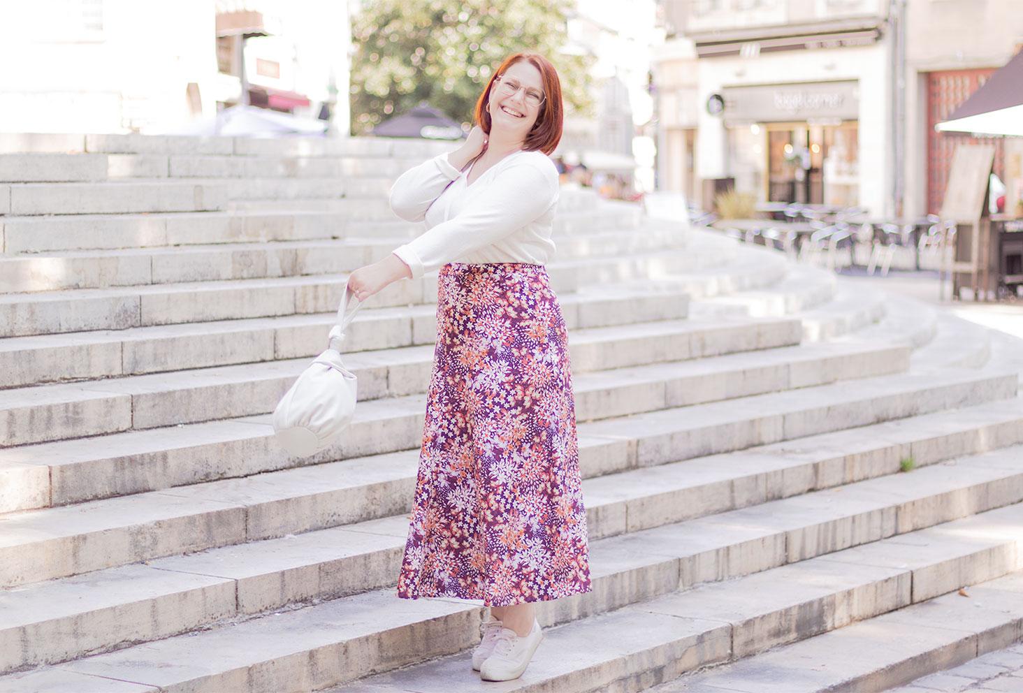 Debout dans les marche avec le sourire, en jupe longue à fleurs rose et pull blanc, le sac lancé vers l'avant