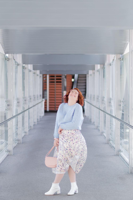 Jupe longue et pull court, avec le sourire, sur la passerelle de la gare de Poitiers