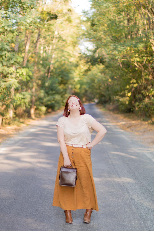 Au milieu d'une route boisée de Montlouis, en camaïeu de marron pour l'automne, avec le sourire et une main sur la hanche