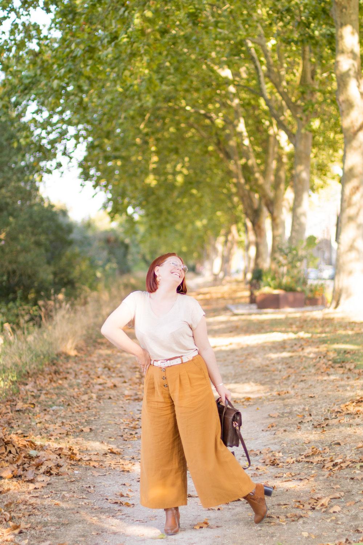 Sur les bords de Loire avec le sourire, en pantalon large camel et t-shirt beige, un sac vintage marron dans la main gauche