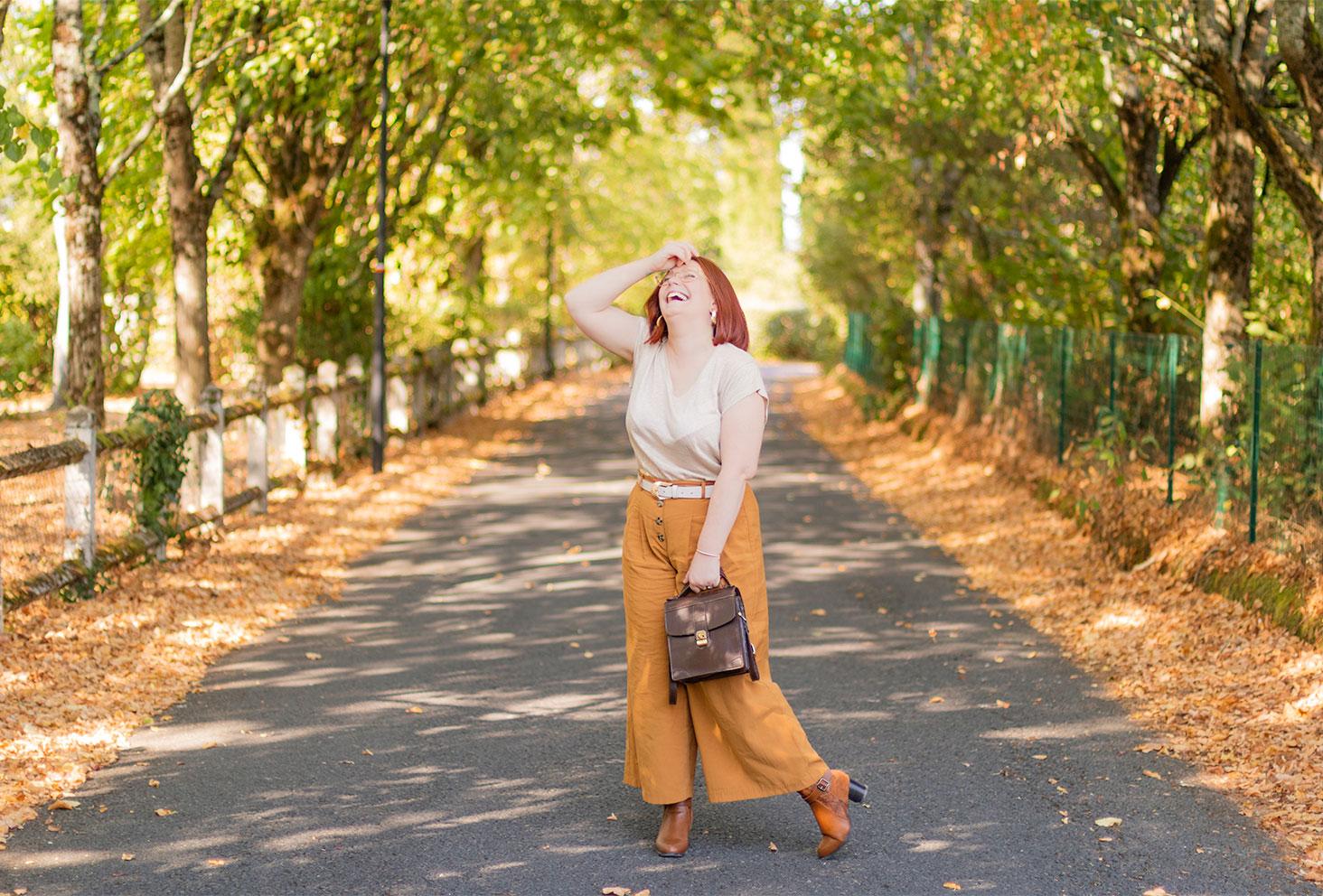 Au milieu d'une rue boisé aux couleurs de l'automne, à Montlouis sur Loire, en pantalon large et t-shirt en lin