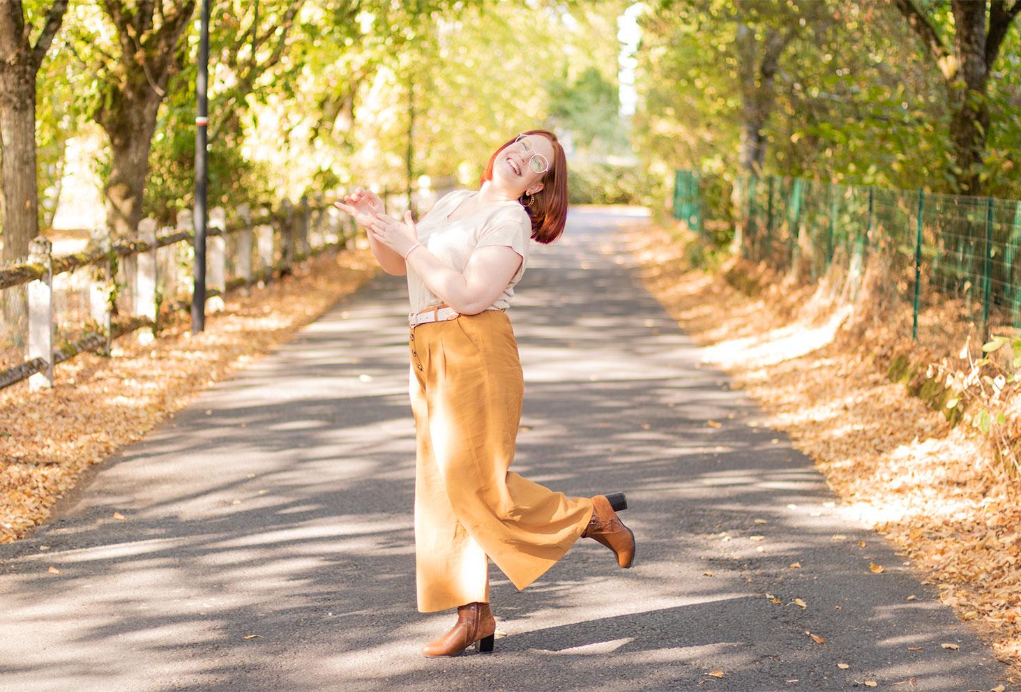 Dans une rue de Montlouis en pantalon large marron et t-shirt fluide, avec le sourire et une jambe levée, de profil