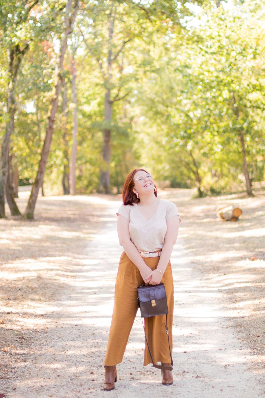 Dans un parc avec le sourire, en pantalon large marron et t-shirt beige, un sac vintage marron entre les main