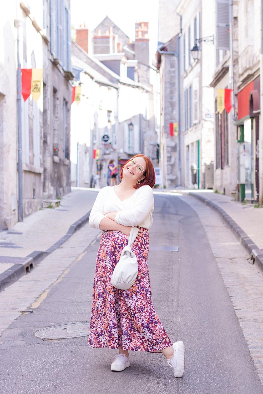 Dans la rue les bras croisés avec le sourire, en jupe longue fleurie et pull blanc