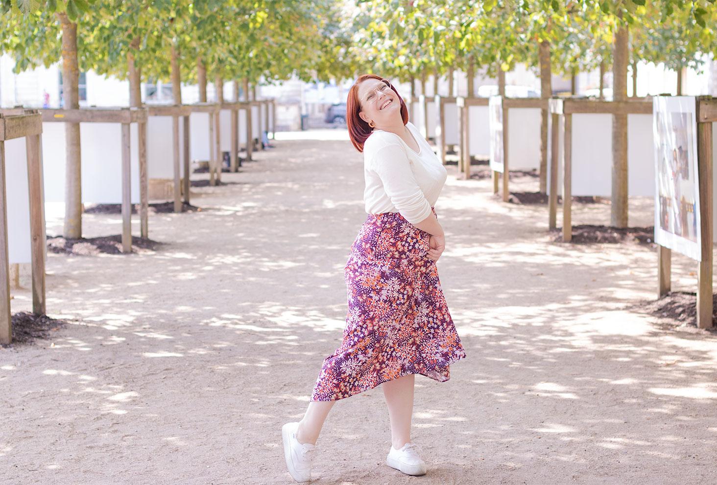 Dans un parc en jupe longue rose et pull blanc, avec le sourire, le bas de la jupe tenue entre les mains devant