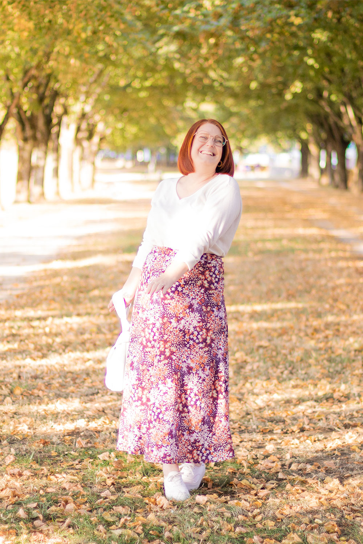 Au milieu d'une chemin boisé avec le sourire, en jupe longue, pull blanc, et baskets à plateformes