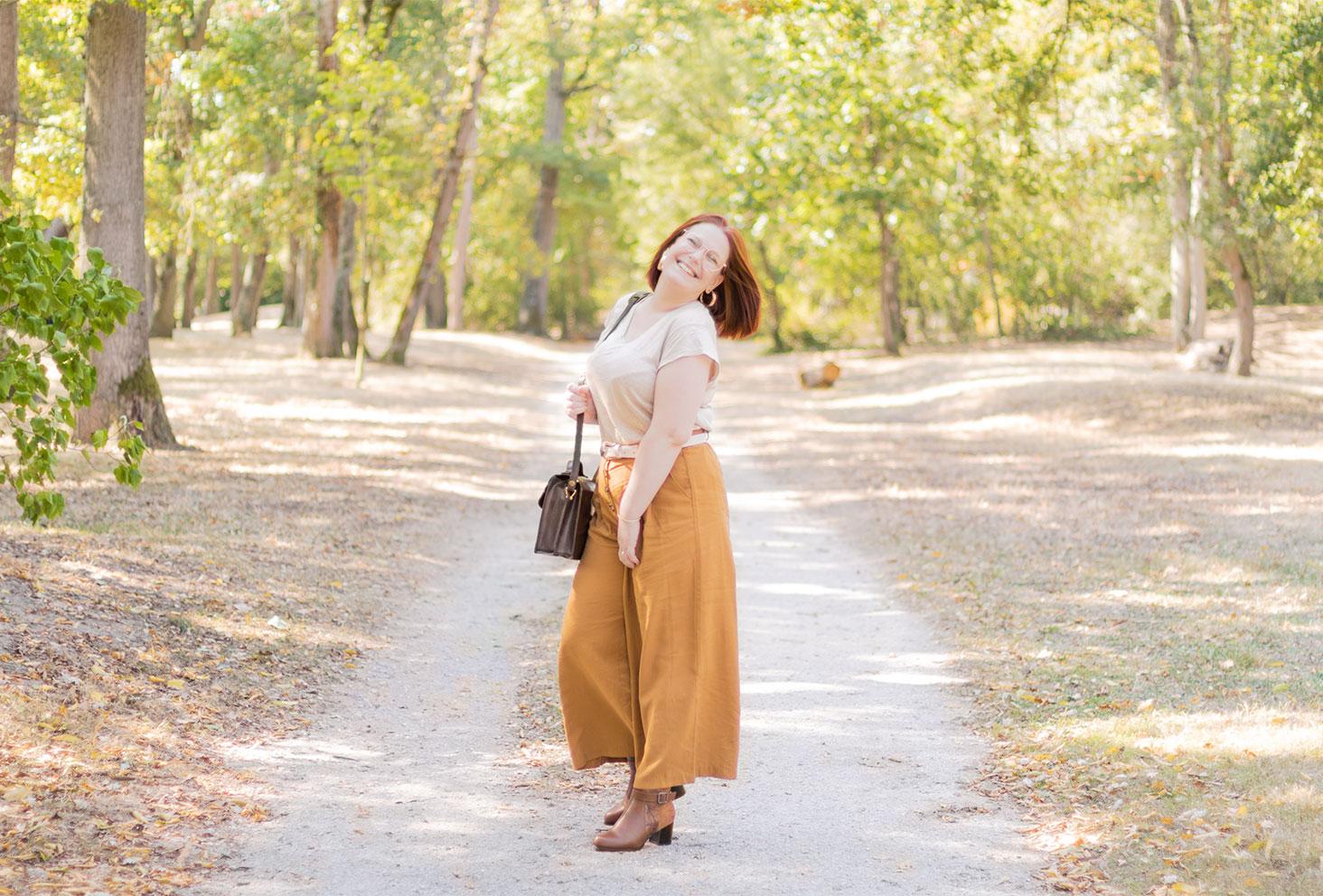 Au milieu d'un parc boisé de Montlouis, en pantalon large marron et t-shirt en lin, un sac vintage sur l'épaule avec le sourire