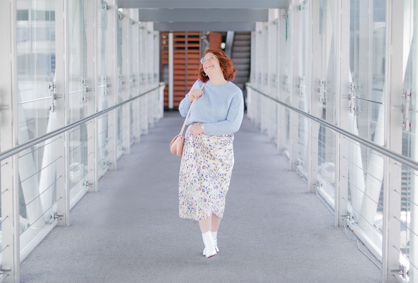 Sur une passerelle street en tenue pastel, jupe longue et pull court, des bottines dans les pieds avec le sourire