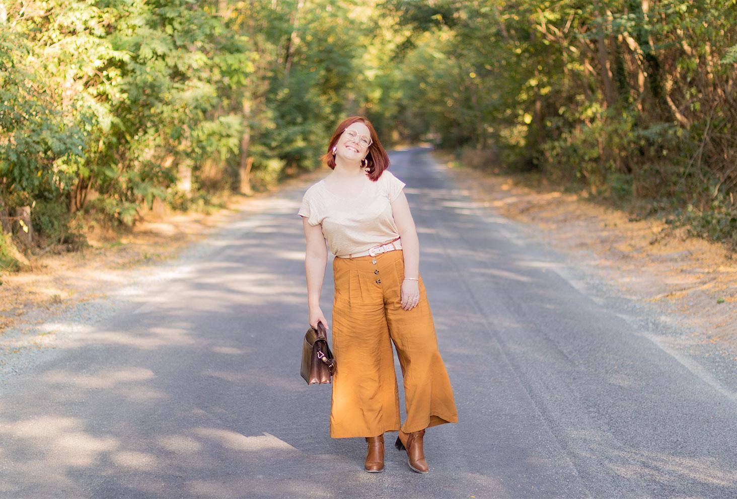 Au milieu des bois de Montlouis sur la route, en pantalon large et t-shirt beige, avec le sourire